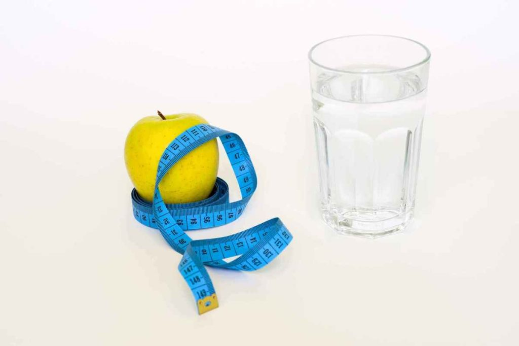 glass of water and tape measure to control calories