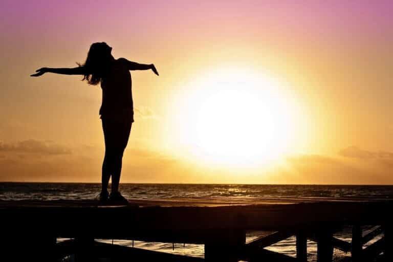 woman stand front the sunset to feel stress free