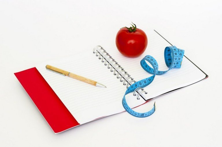 notebook and tape measure for weight loss plan
